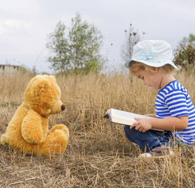 Toddler reading to bear