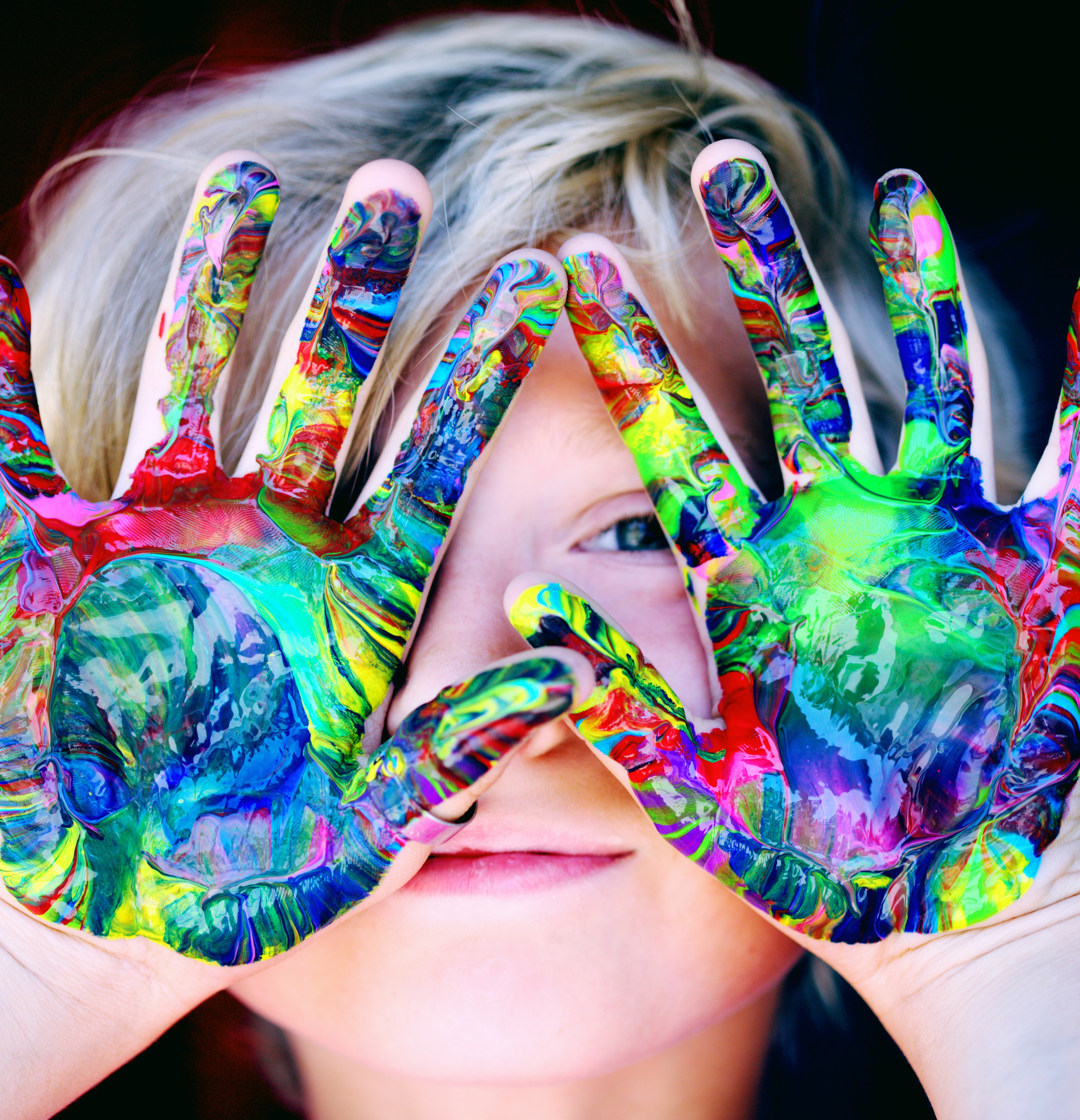 Image of a child with hands covered in paint