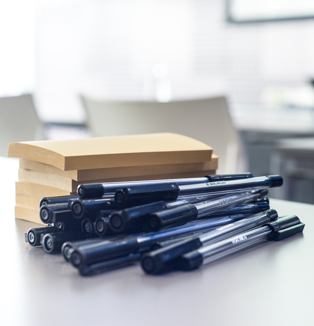 Image of a pile of pens and post-it notes