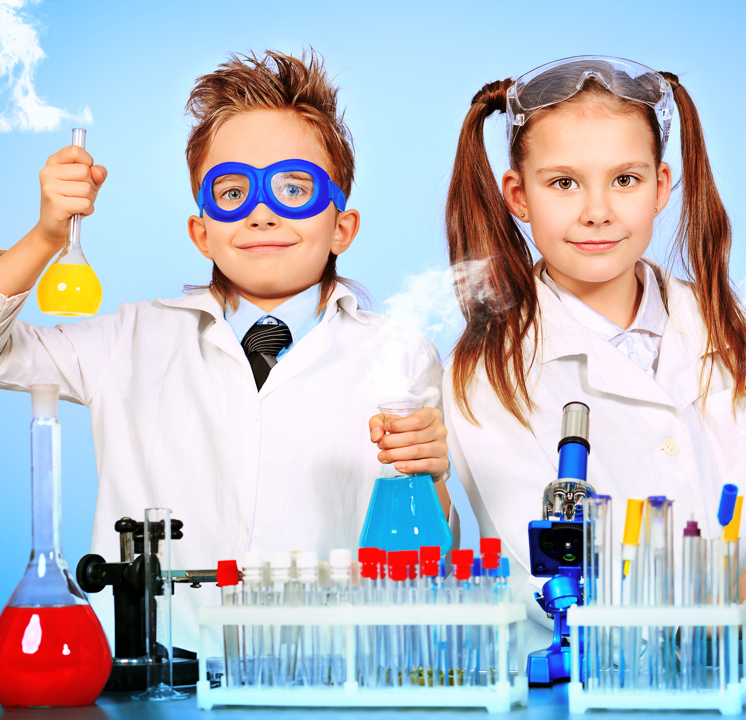 Little kid scientists in white lab coats.