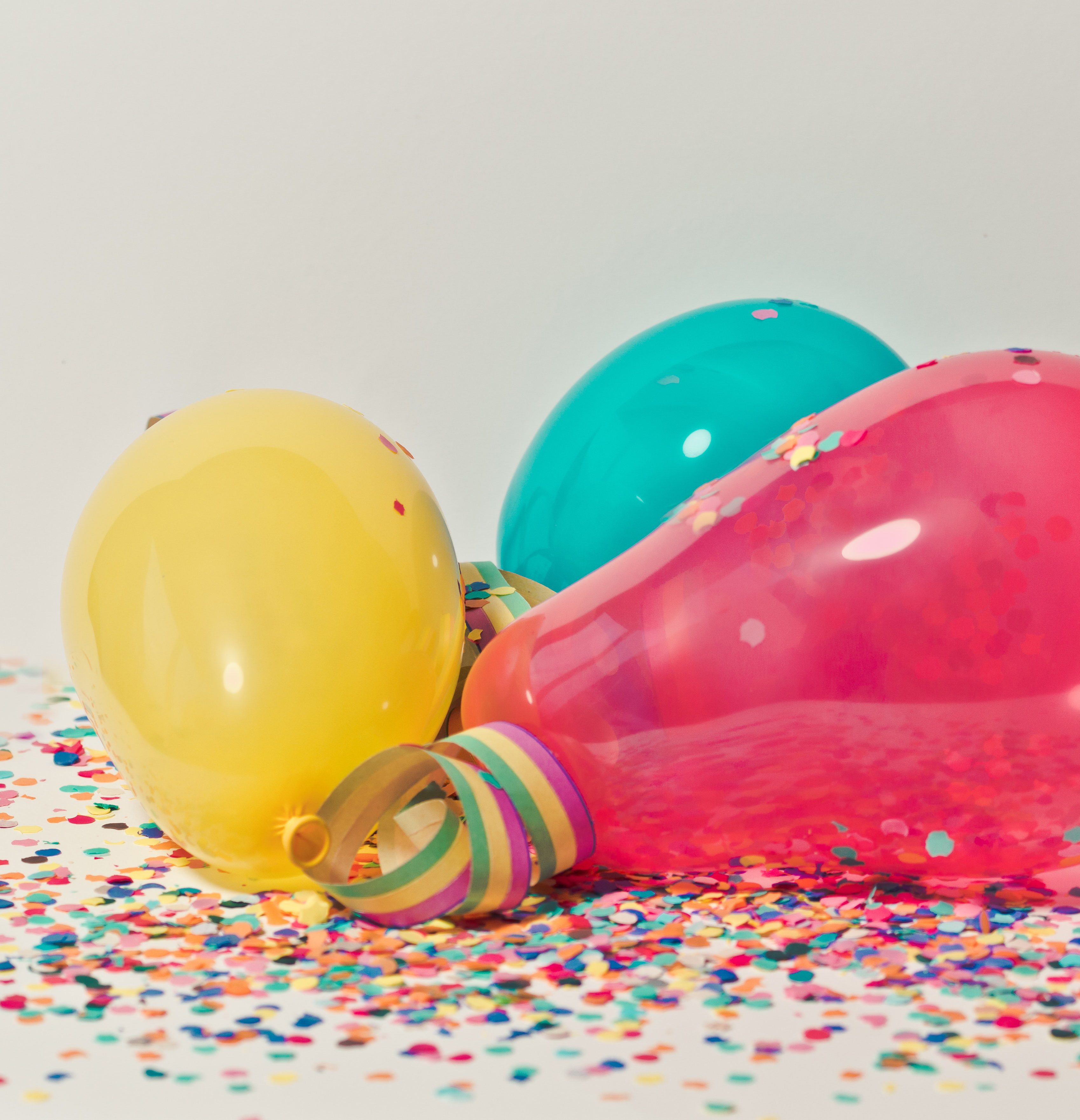 yellow, blue and pink balloons on confetti