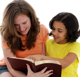 Photo of child reading with teen