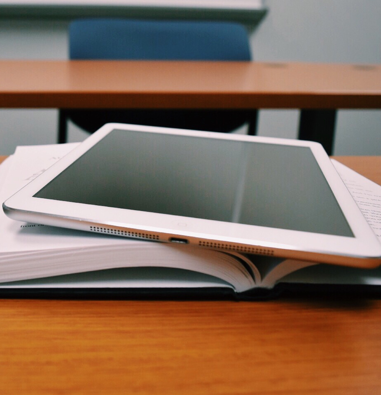 tablet resting on top of open book