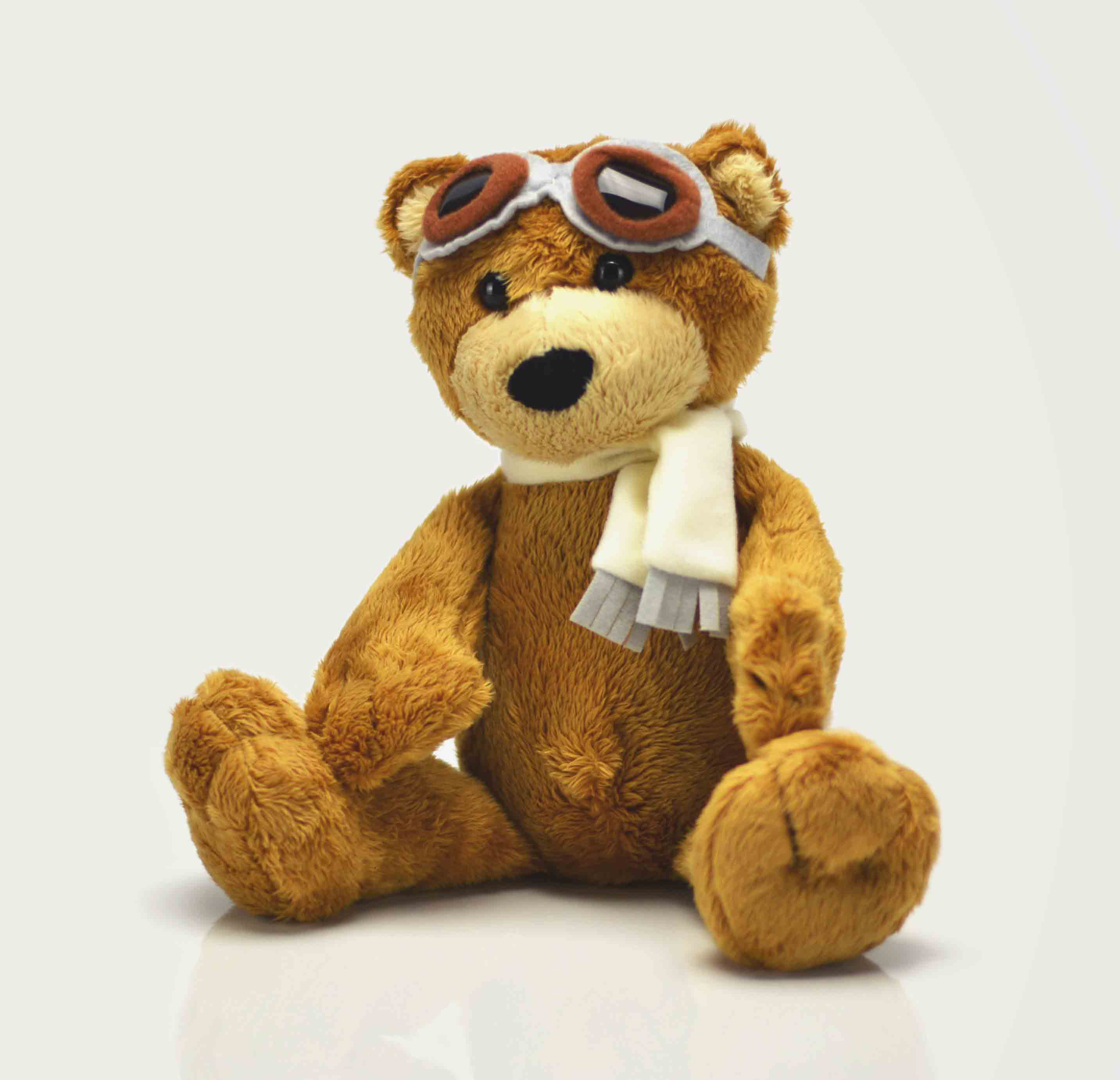 A stuffed brown teddy bear wearing goggles and a scarf