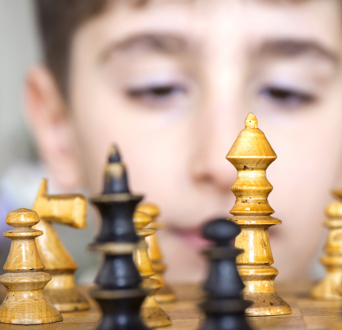 A child looking at chess pieces on a board