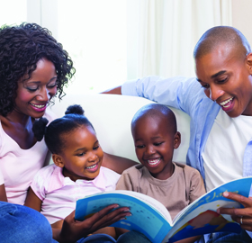 family reading a picture book together on couch