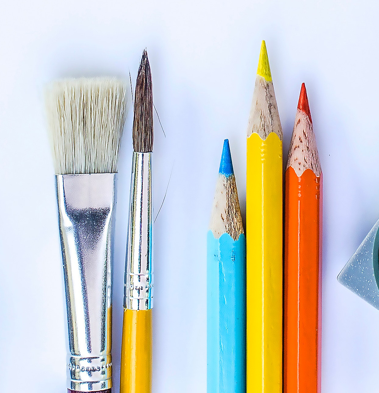 A photograph of two clean paintbrushes and blue, yellow and orange coloured pencils