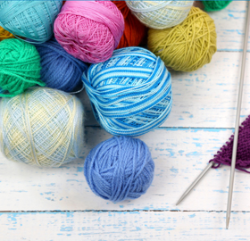 A pile of multicoloured balls of yarn with two needles