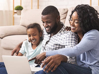 Family sitting on the couch looking at a laptop