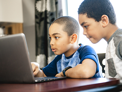 Two children looking at a computer
