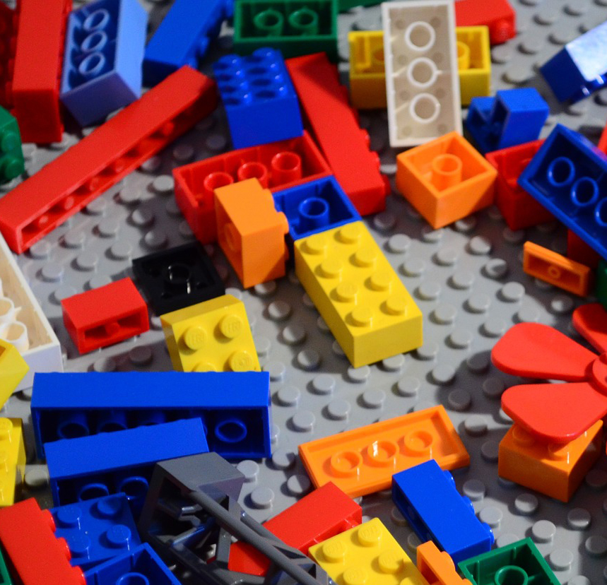 A collection of miscellaneous LEGO bricks on a gray LEGO mat