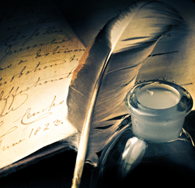 A quill, ink well and open book