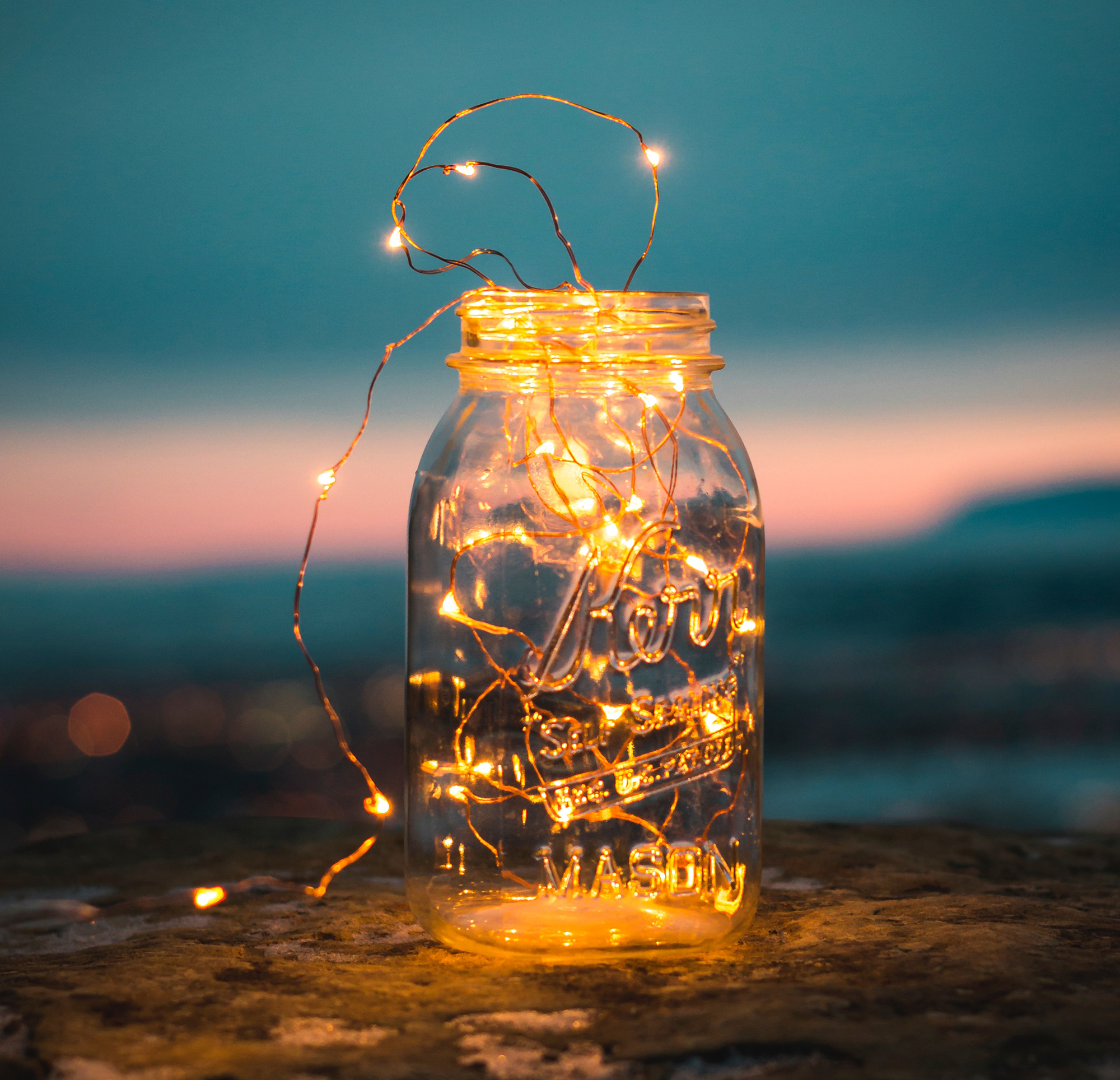 A mason jar filled with a string of tiny lights