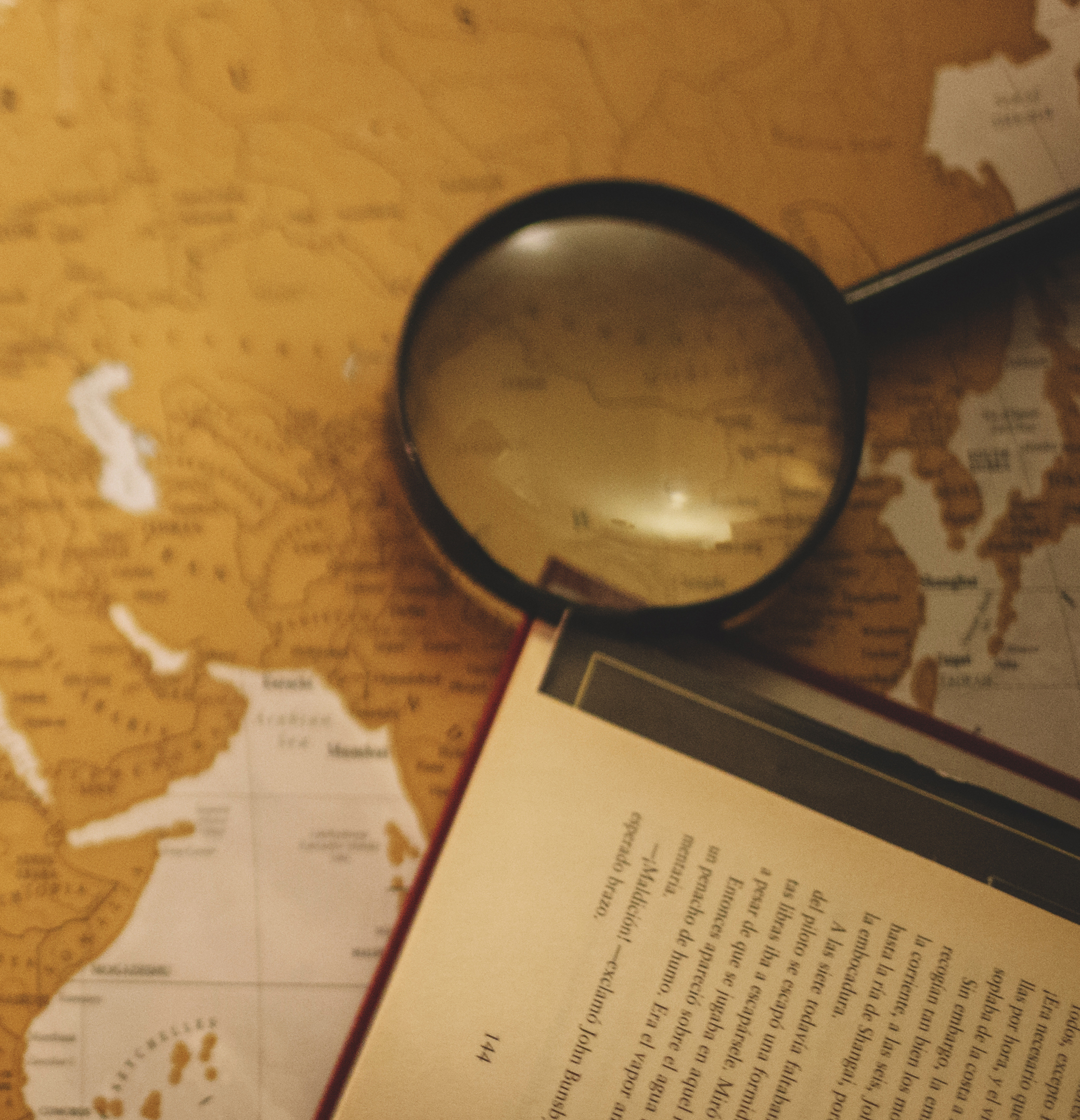 Photograph of a magnifying glass, an open book and a map