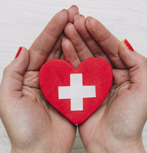 woman's hands holding red heart with white cross symbol