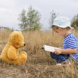 child with book and bear