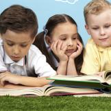 Two boys and a girl looking at open books