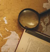 A magnifying glass and open book laying on a map